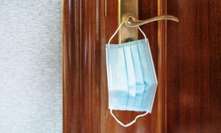 Mascarilla colgada en la manija de una puerta