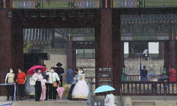 Visitantes al palacio Gyeongbok se protegen de la lluvia